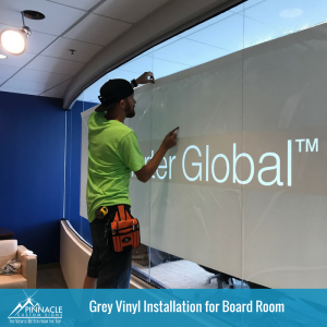 Grey Vinyl Window Graphic for Charter Global Signage Being Installed