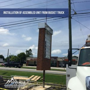 A bucket truck picks up the sign frame and puts it over the steel post for installation