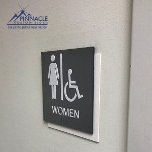 Raised letters, braille, and high contrasting restroom signs are ADA compliant